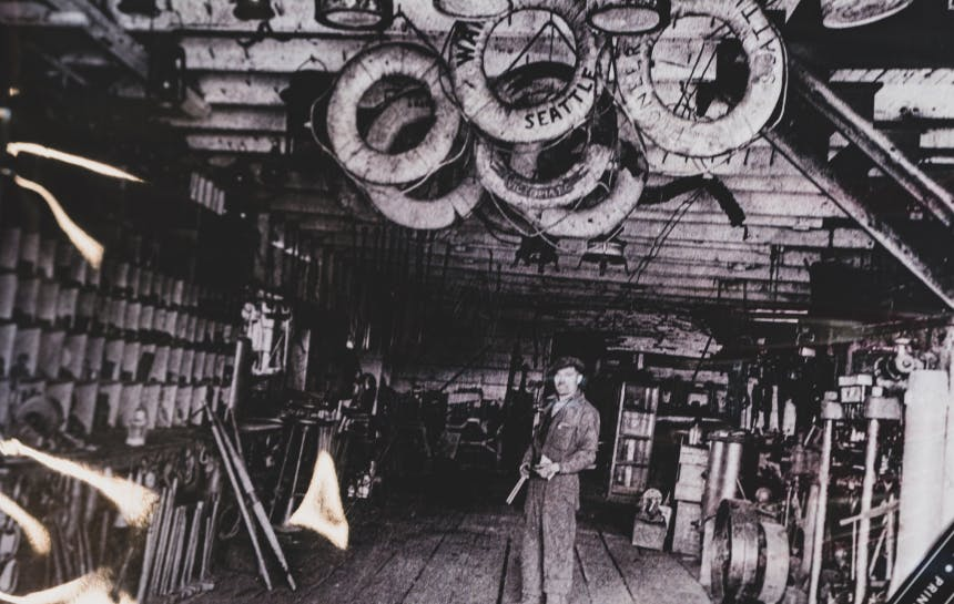black and white image of man standing in a workshop under a collection of life floats hanging by the rafters