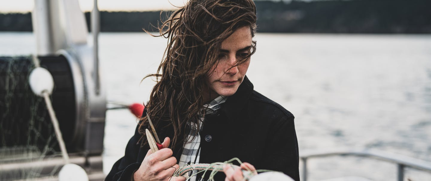 woman in black coat holding a floater on a fishing net while standing on a boat