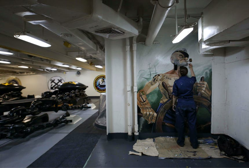 person in a nautical museum painting a mural of popeye