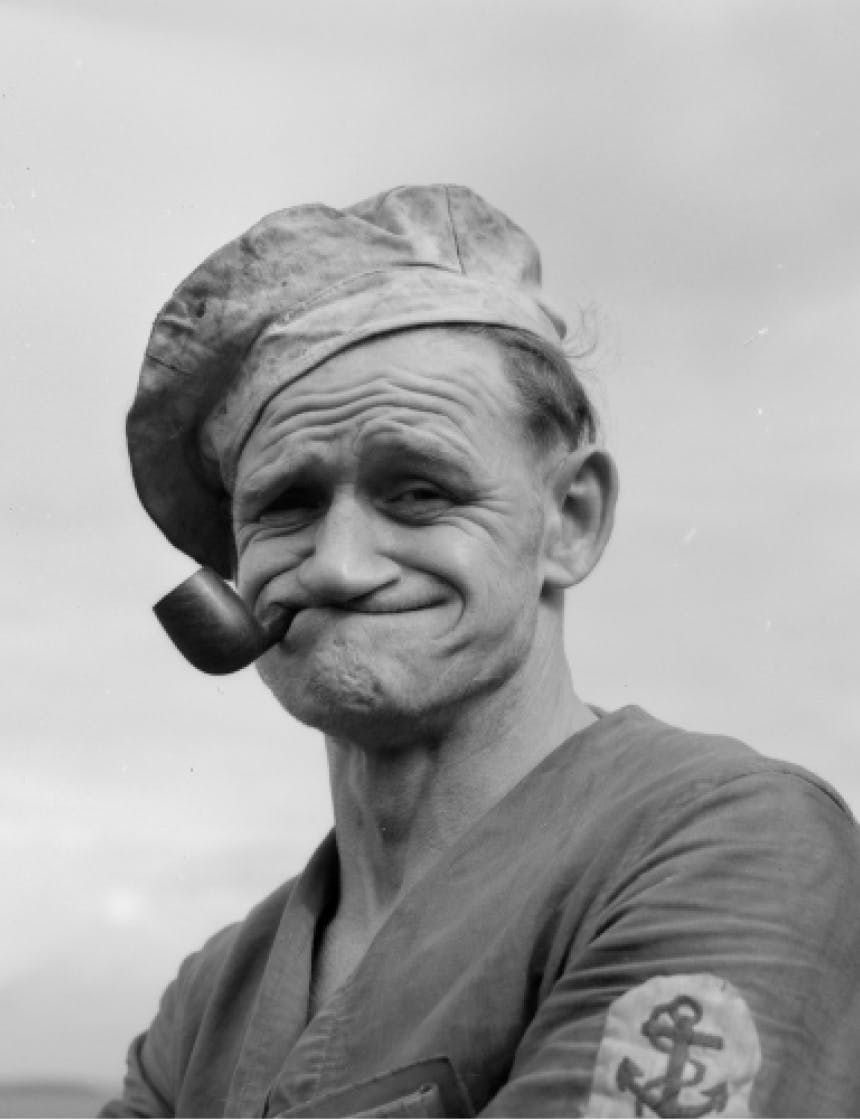 old black and white image of a sailor smoking a pipe with a face evocative of popeye