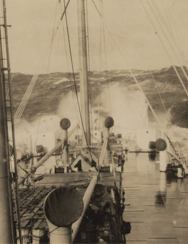 black and white image of the bow of a ship dipping into rough seas sending ocean spray into the sky