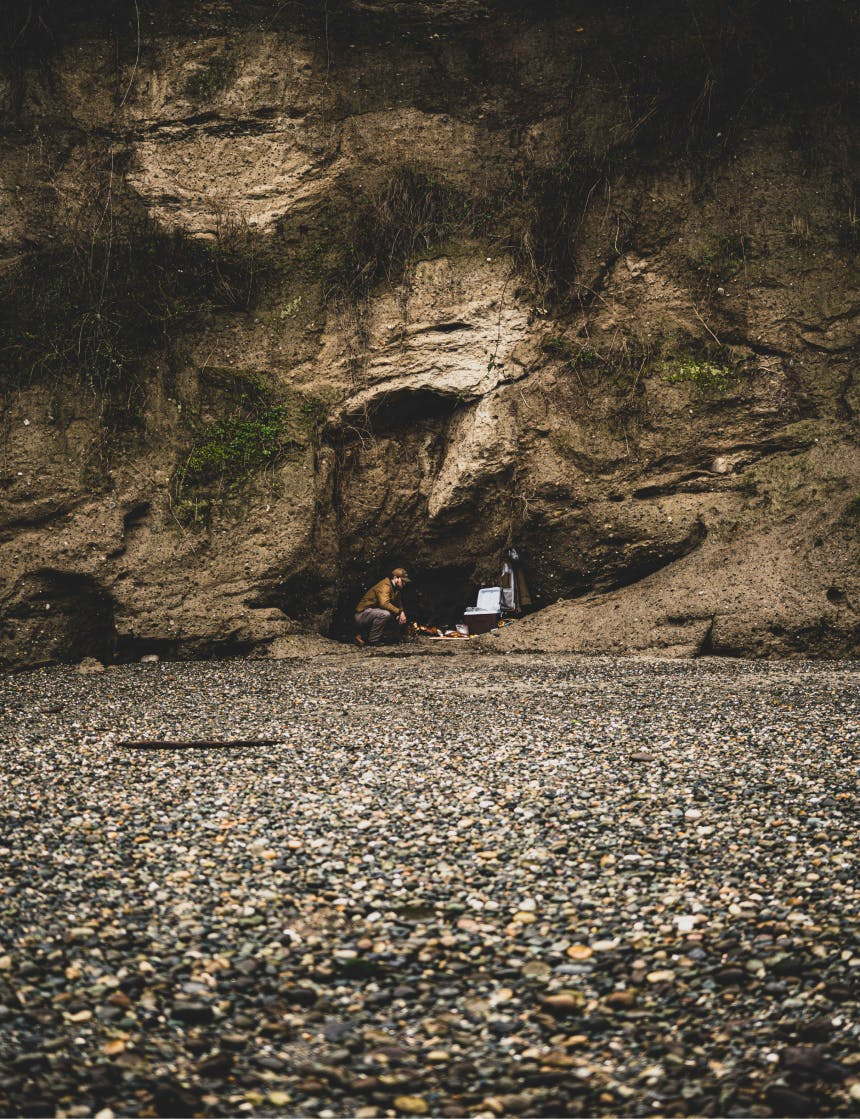 person tending to a fire on a rocky beach in a small stone cave alcove