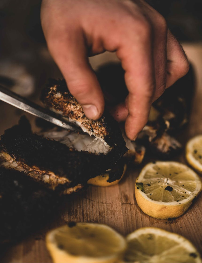 knife cutting rock fish meat off a roasted rockfish next to lemon slices