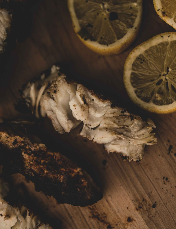 white rockfish meat next to lemon slices