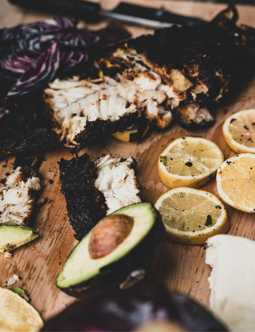 rockfish meat with spice rub next to lemon slices, and halved avocado on cutting board