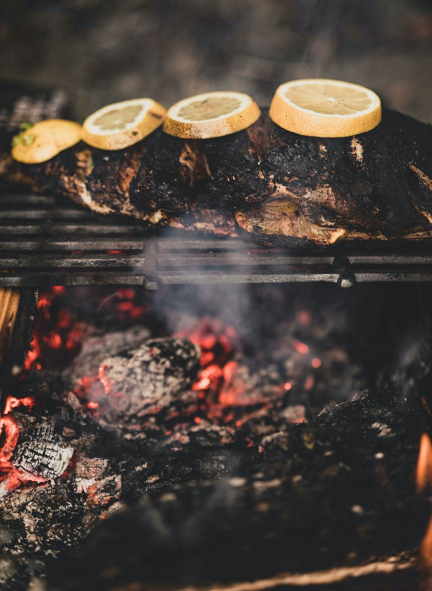 rockfish roasting on grate over coals with lemon slices on top