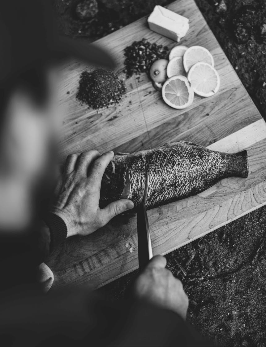 hand securing a rockfish while a knife cuts a filet on a wooden cutting board next to slices of lemons, spices, and butter
