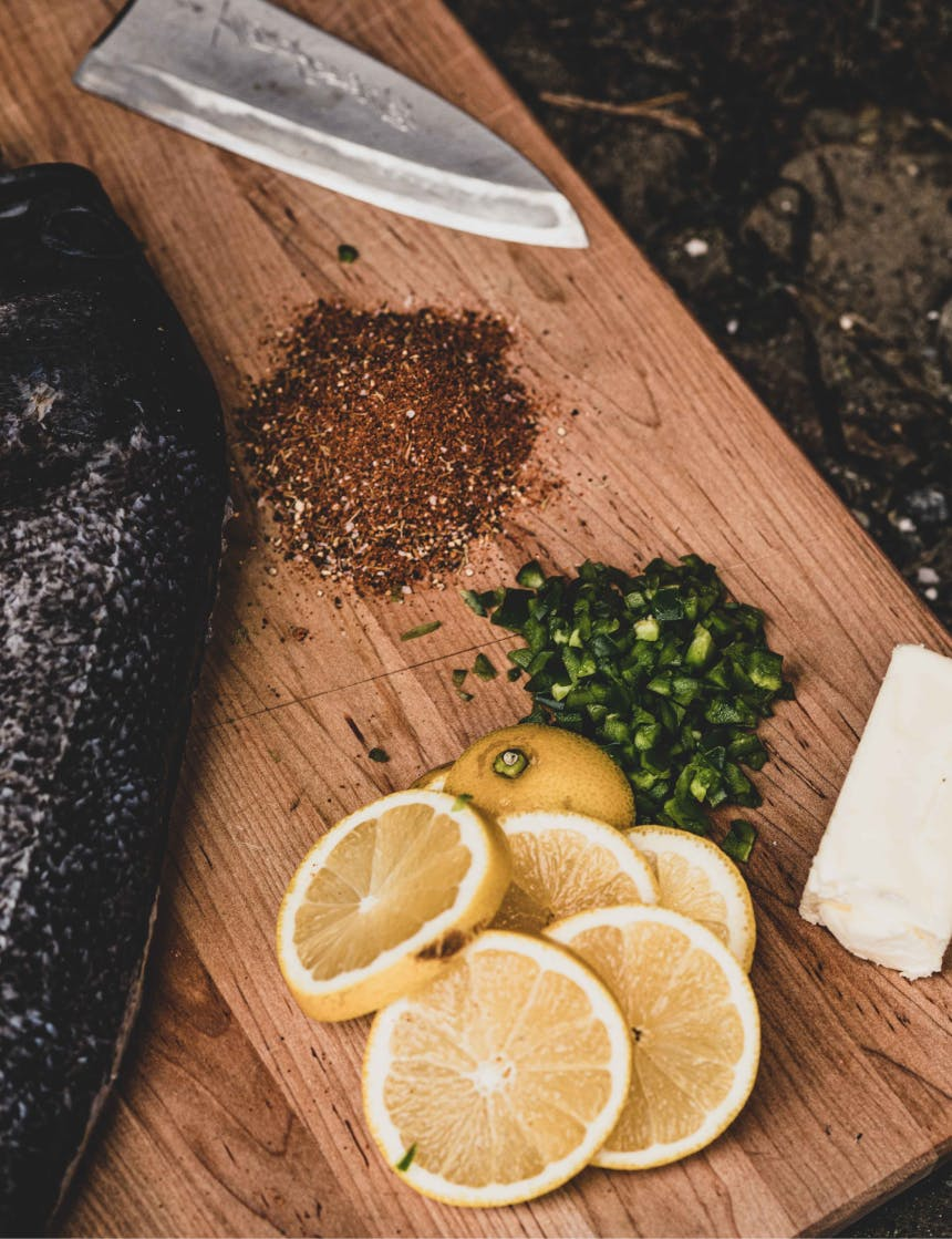 knife, spices, rockfish, lemon, butter, and green vegetable on a wooden cutting board