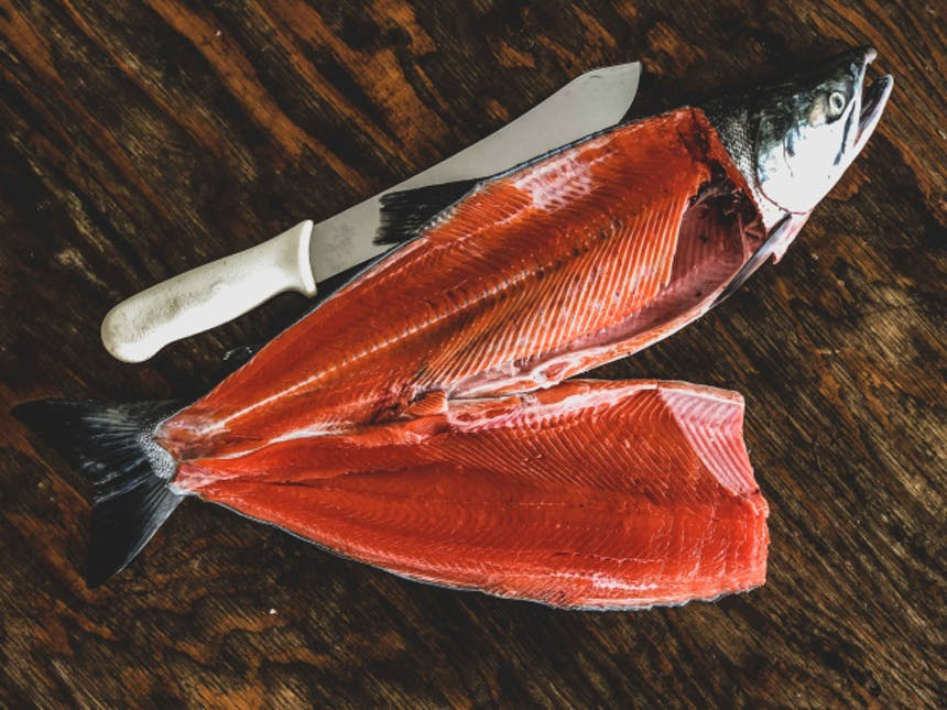 a salmon fileted on a wood surface next to a knife, head on