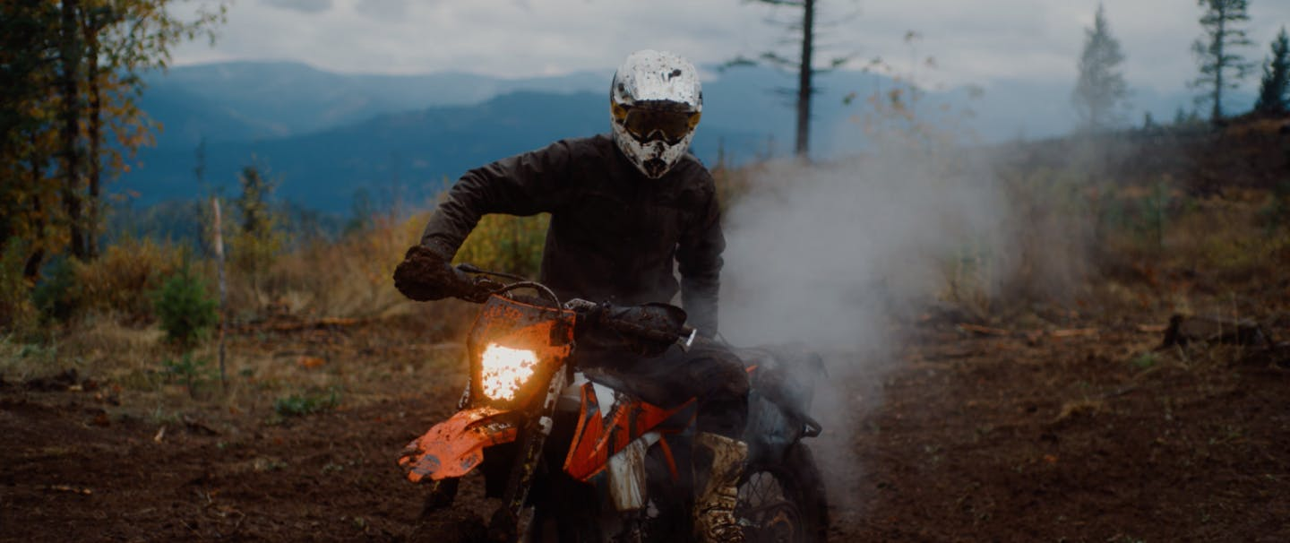 person in mud spattered white helmet riding a dirt bike in a pine forest clearing kicking up smoke from exhaust