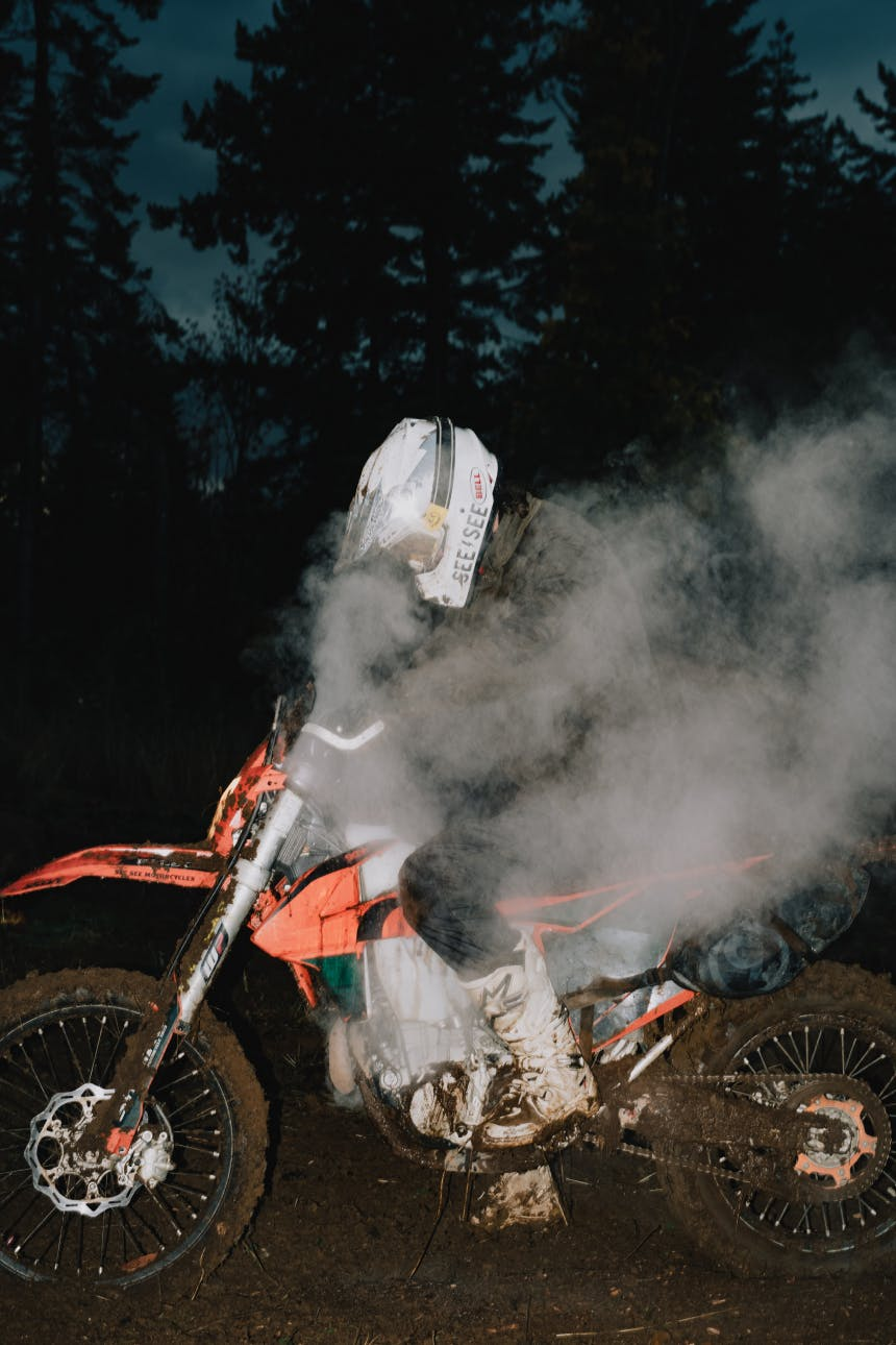 person in white motorcycle helmet sitting on a smoking orange motorcycle covered in mud