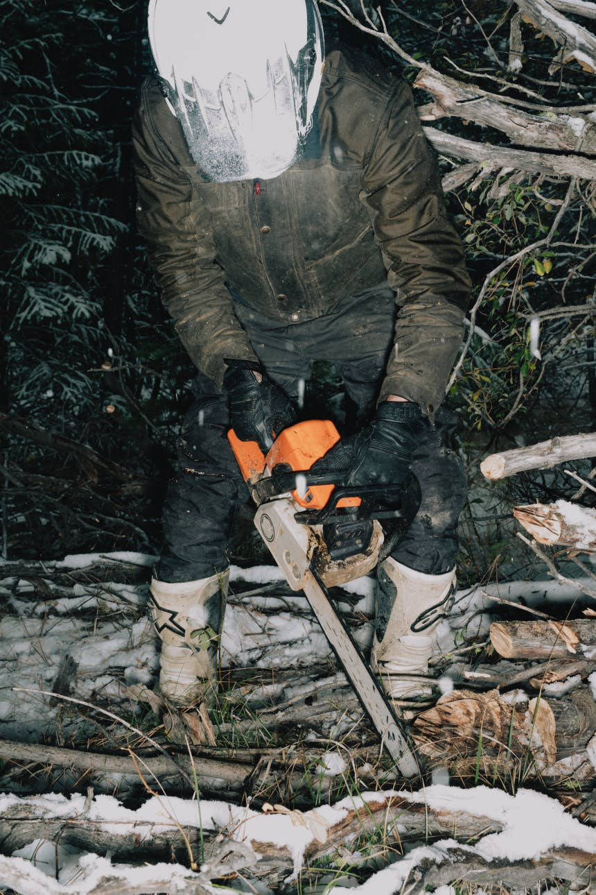 person in brown coat and black pants and motorcycle helmet cutting wood with an orange chainsaw