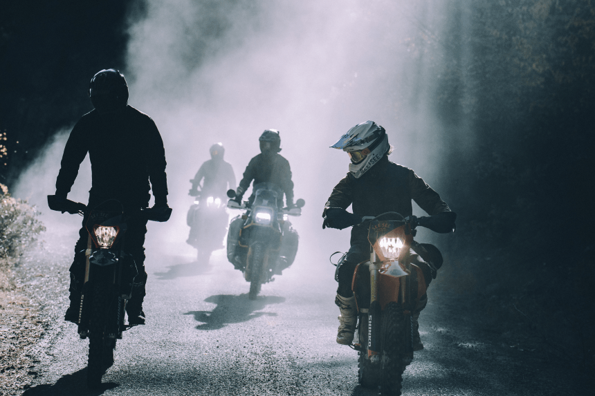four people riding their motorcycles down a mud road in the forest bathed in fog