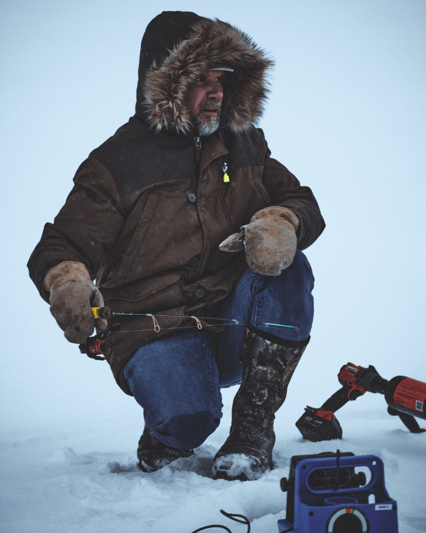 man tan gloves and fur lined parka kneeling by an ice fishing hole holding a fishing rod