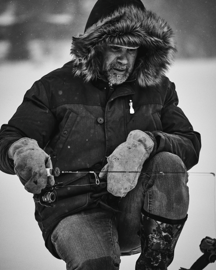person with tan mittens and a fur lined parka holding a fishing rod kneeling