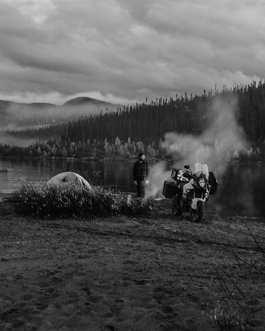 person standing by their motorcycle and a campfire billowing smoke at the foot of a lake in a pine forest