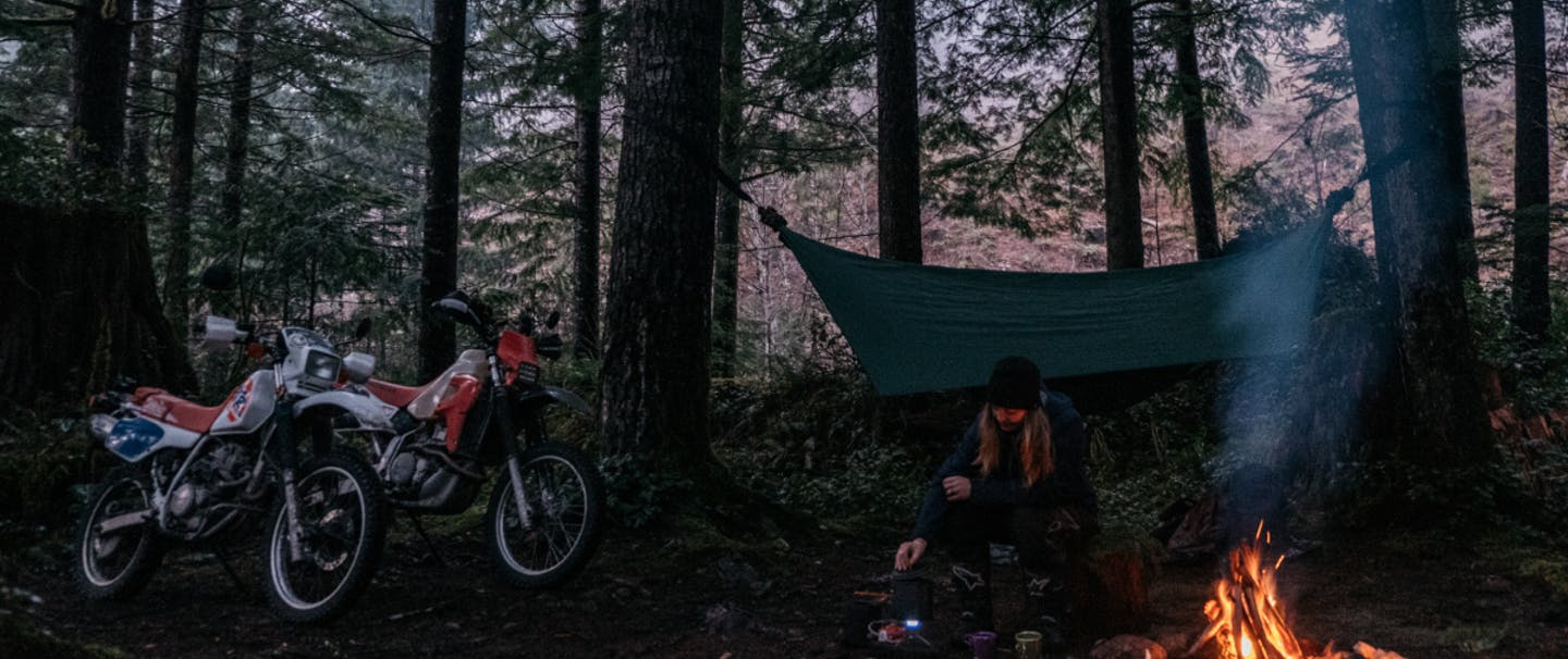 person squats next to a fire in a campsite with two dirtbikes and pinetrees