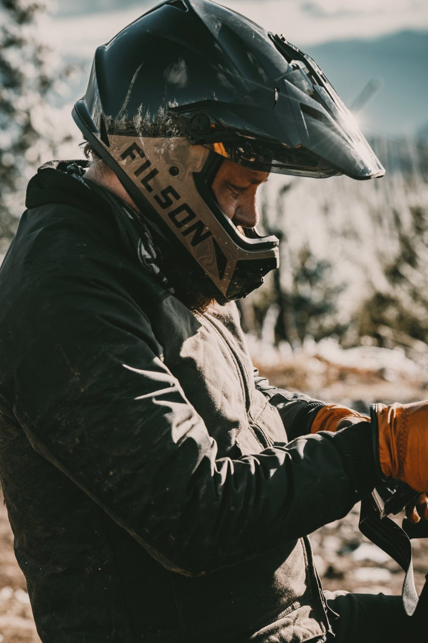 person in a filson motorcycle helmet in the forest