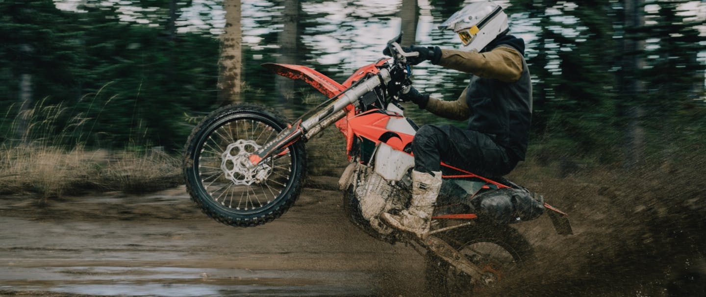 person popping a wheelie on an orange motorcycle on a muddy road in the forest
