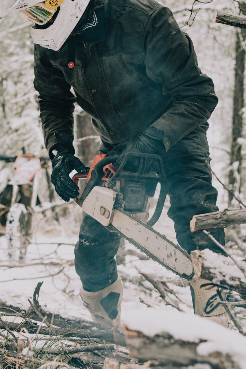 person in black black jumpsuit using a chainsaw in a snowy forest with a white motorcycle helmet on