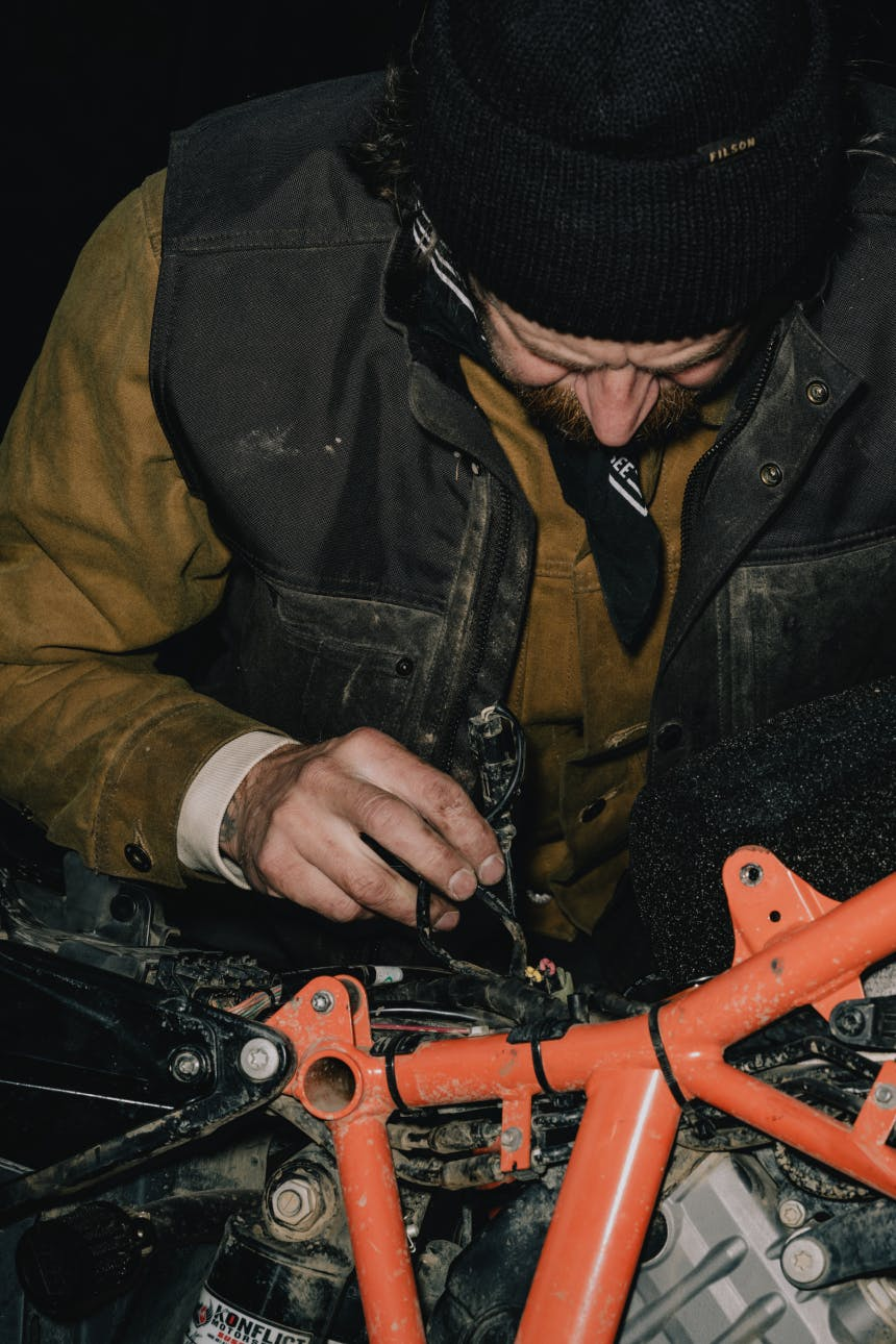 person working on the frame of an orange motorcycle