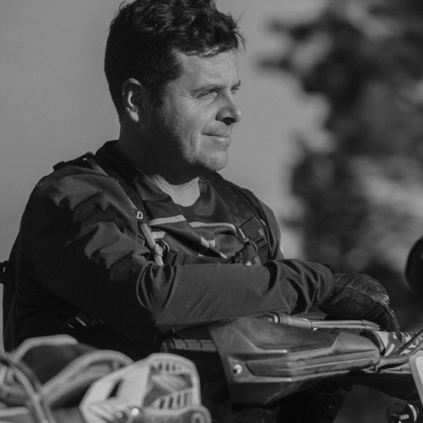 man in black jacket with arm resting on the handlebars of a motorcycle