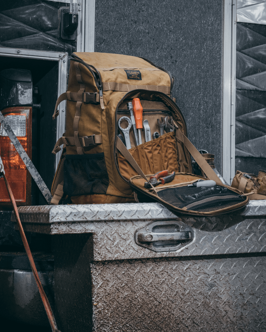 tan filson bag containing tools sitting on a truck tailgate toolbox