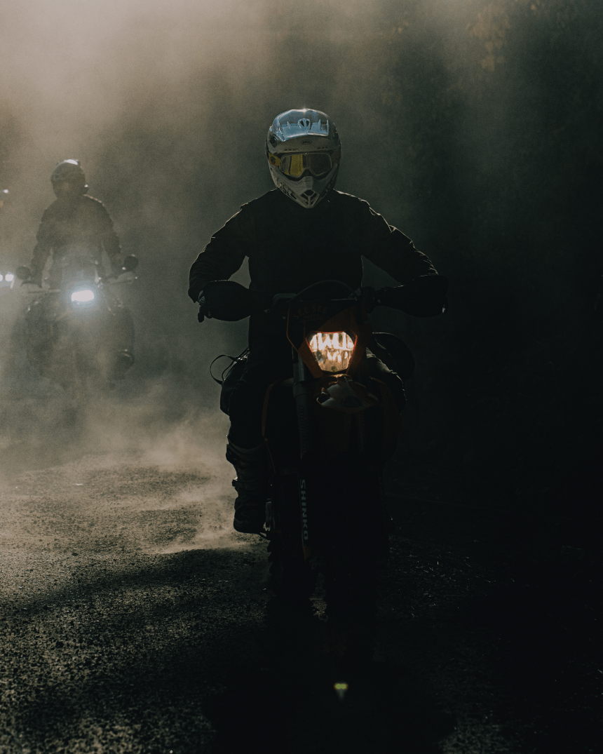 two people riding motorcycles on a foggy dirt road at dawn