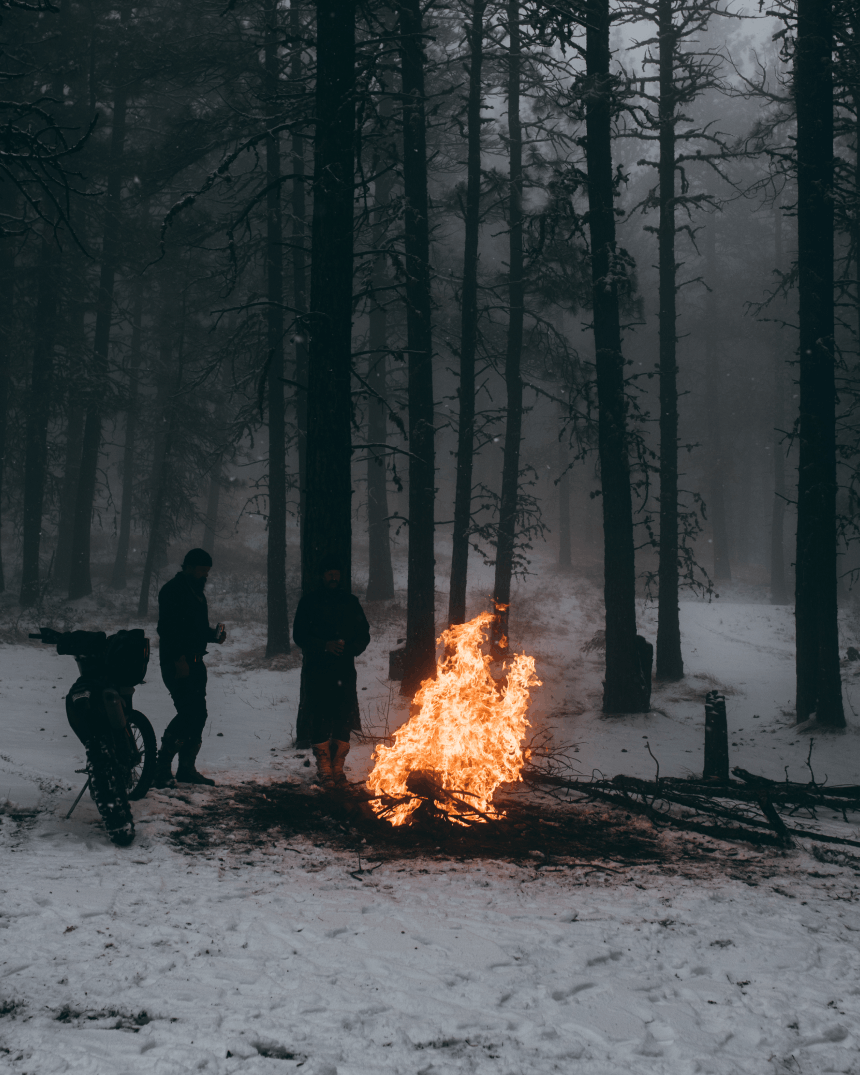people in a snowy campsite stand next to a very large fire
