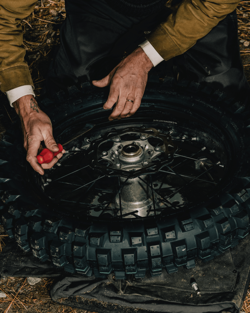 hands use a screw driver to repair a motorcycle tire