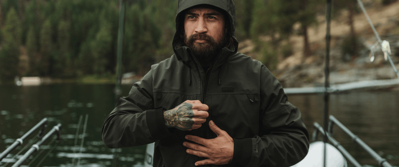 man with tattooed hand zipping up a dark filson coat standing on a boat