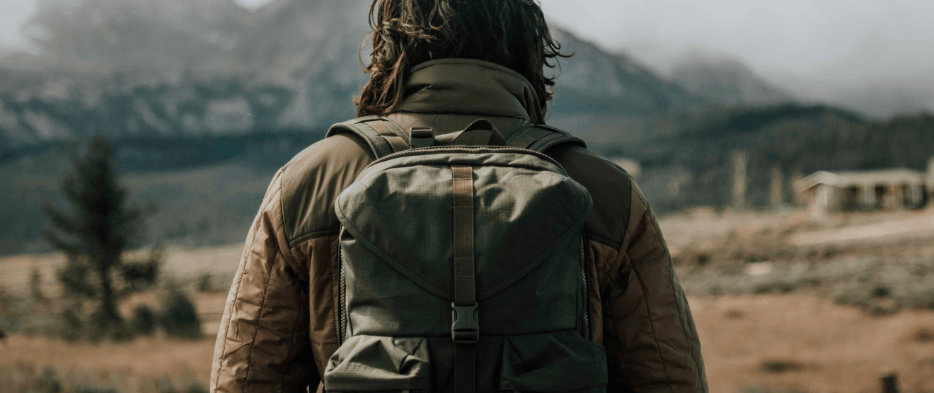 person in olive and tan coat and green filson bag walking toward distant mountains in a high meadow