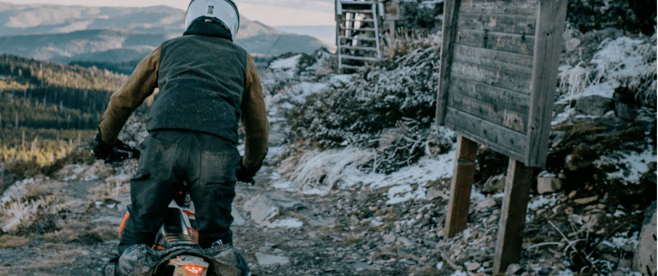 person riding a dirtbike down a snow dusted mountain path near a wooden structure