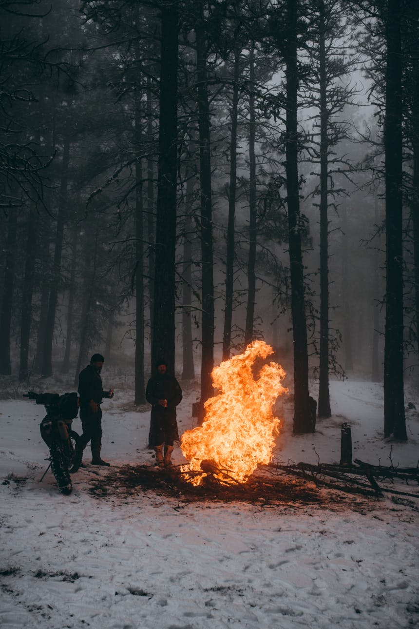 people standing by a motorcycle in a pine forest in a snow covered forest next to a large fire