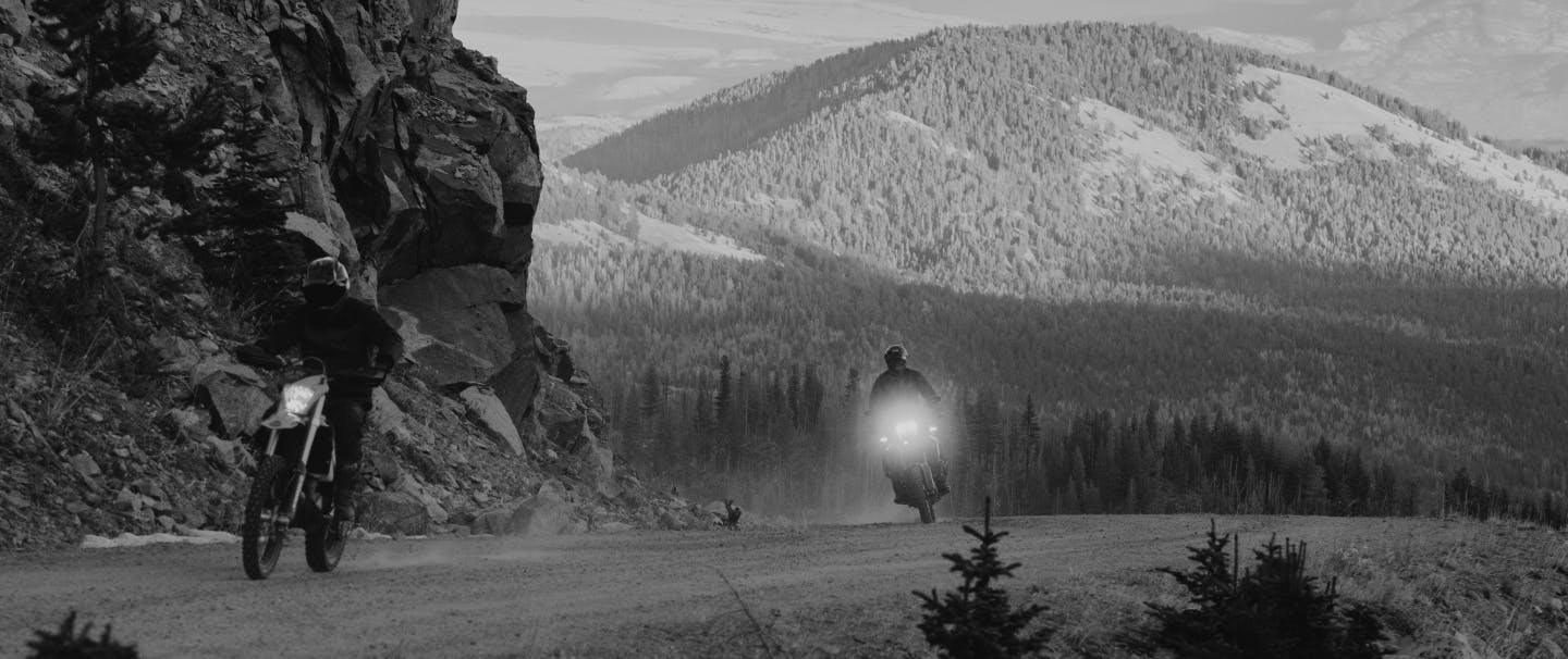 two people riding motorcycles on a dirt road with a pine covered hill in the background