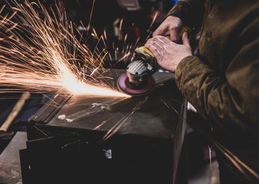 hands using an angle grinder kicking up sparks off the side of an ammo cannister
