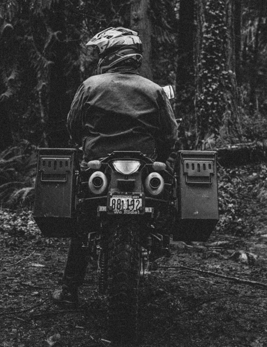 person sitting on motorcycle in the forest with ammunition cannisters mounted to the back wheel