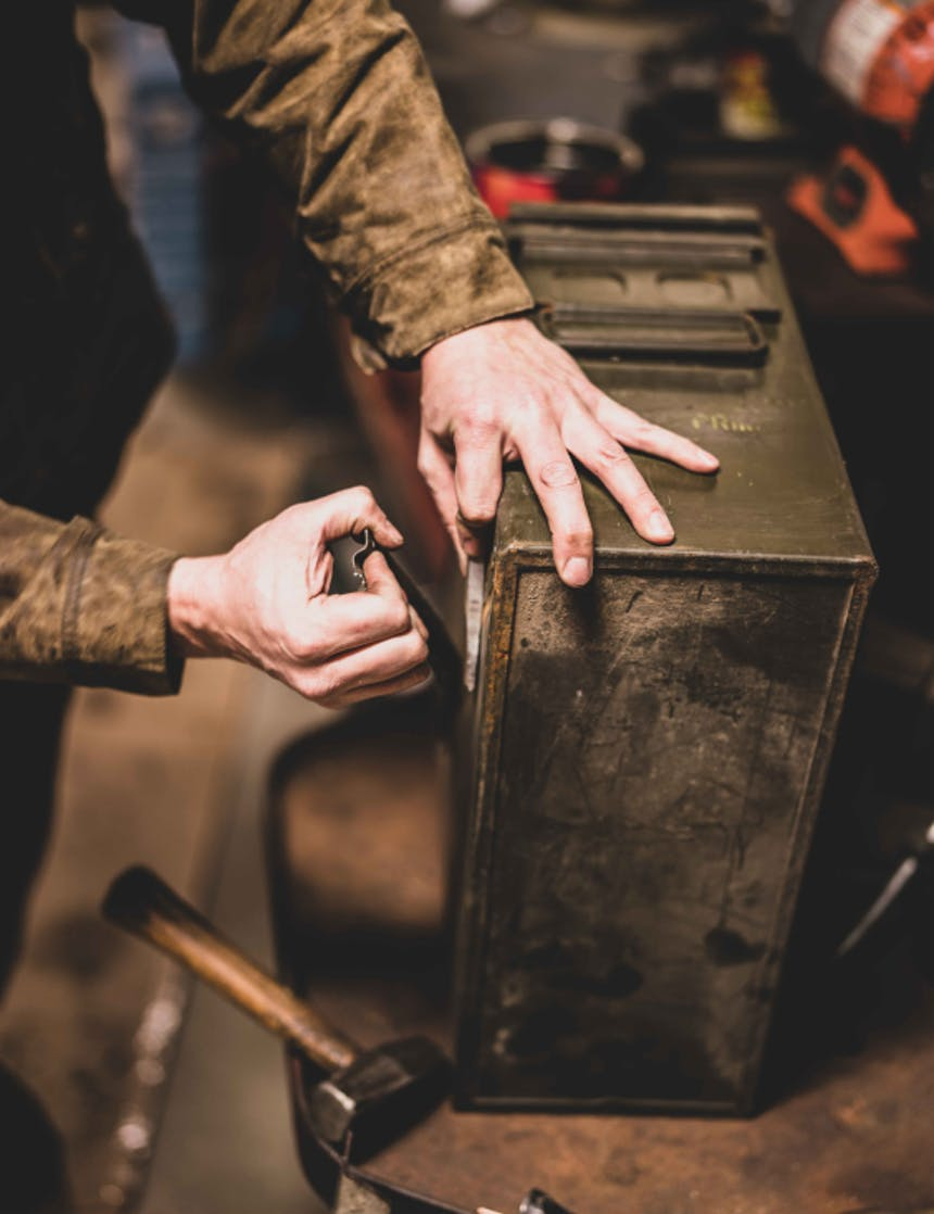 hand prying a metal detail off the side of a green ammo cannister on a workbench