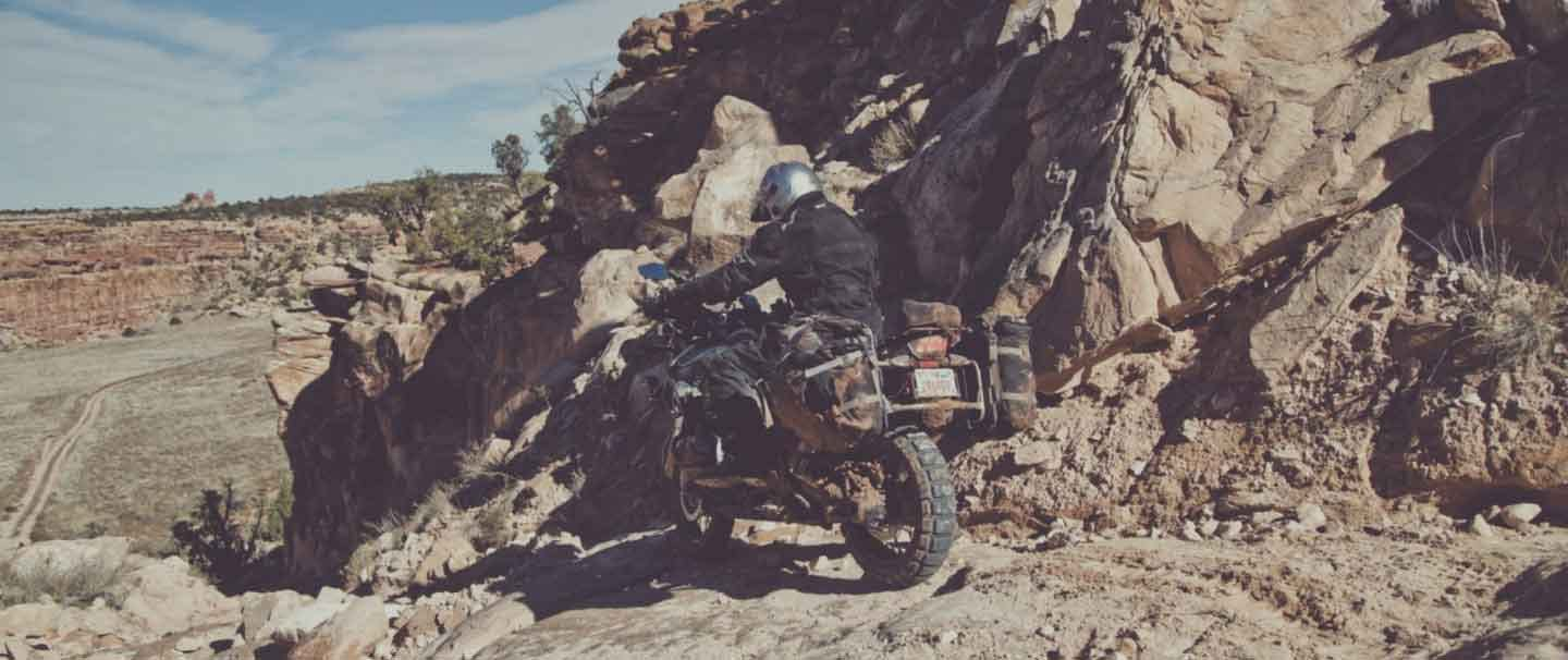person in silver helmet and black jacket riding a motorcycle down a rocky embankment in the high desert of the Utah Canyonlands