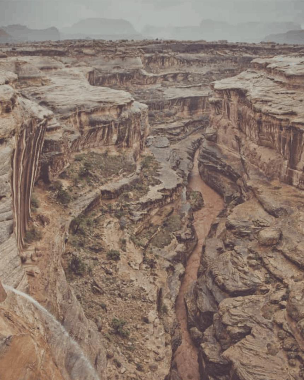 a narrow reddish brown riverr cuts through a deep sandstone canyon