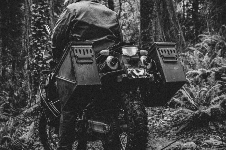 person in helmet and jacket standing motorcycle up in a forest