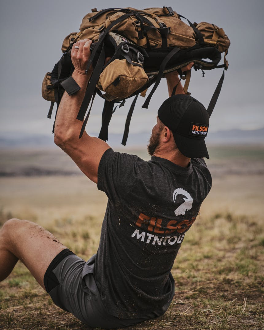 Dustin Diefenderfer performing a Pack Sit-Up Military Press with a 60lb weighted bag.