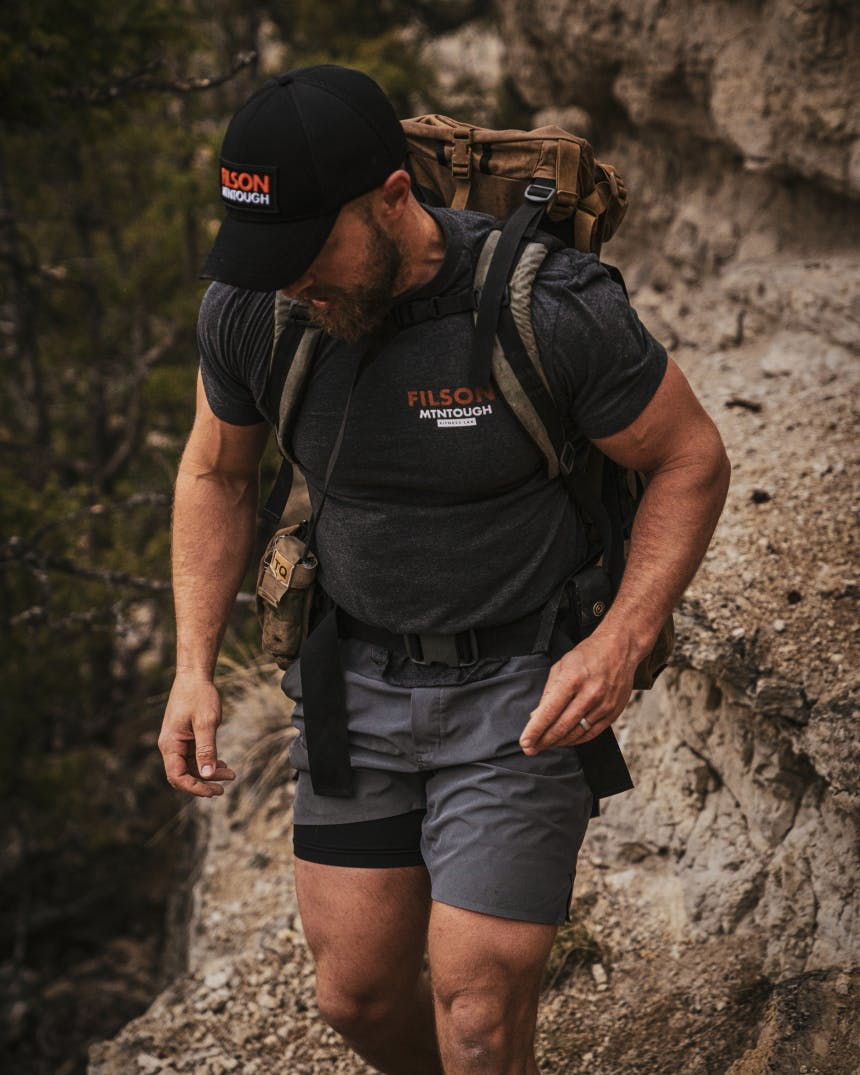 Military looking male running through the Montana wilderness with a weighted backpack.
