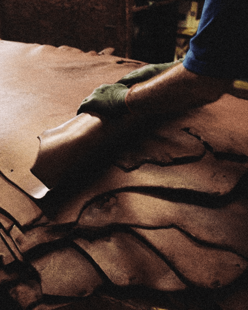 Hands rolling leather hides.