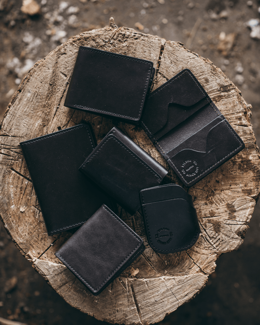 Top down of Filson wallets on a wooden stump.