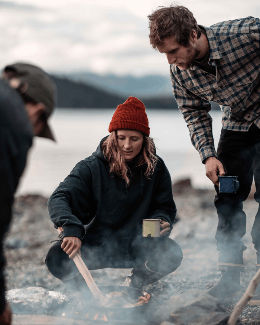 Woman cooking over an open fire on the beach in Alaska.