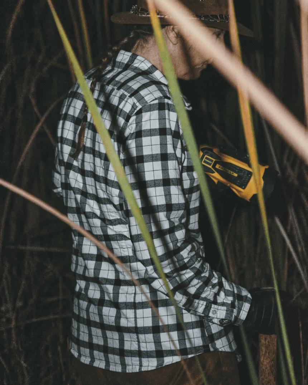 Woman in heavy brush wearing Filson clothing.
