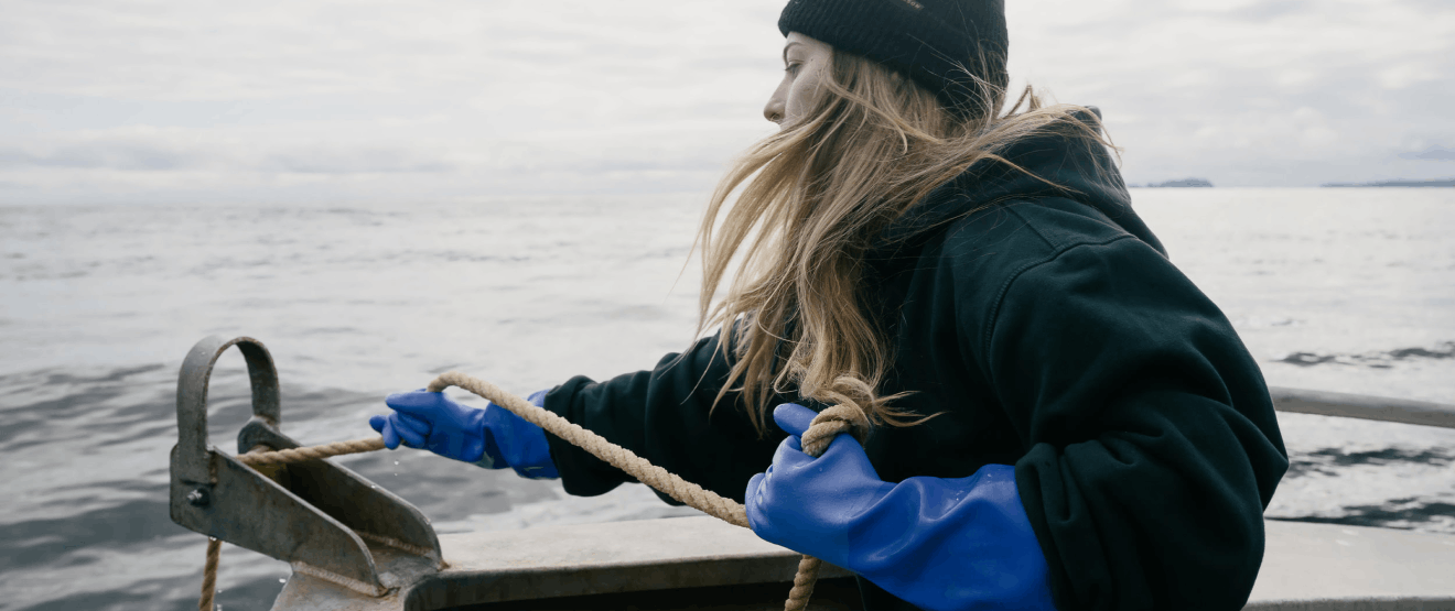 Young woman on a fishing boat pulling a line in.