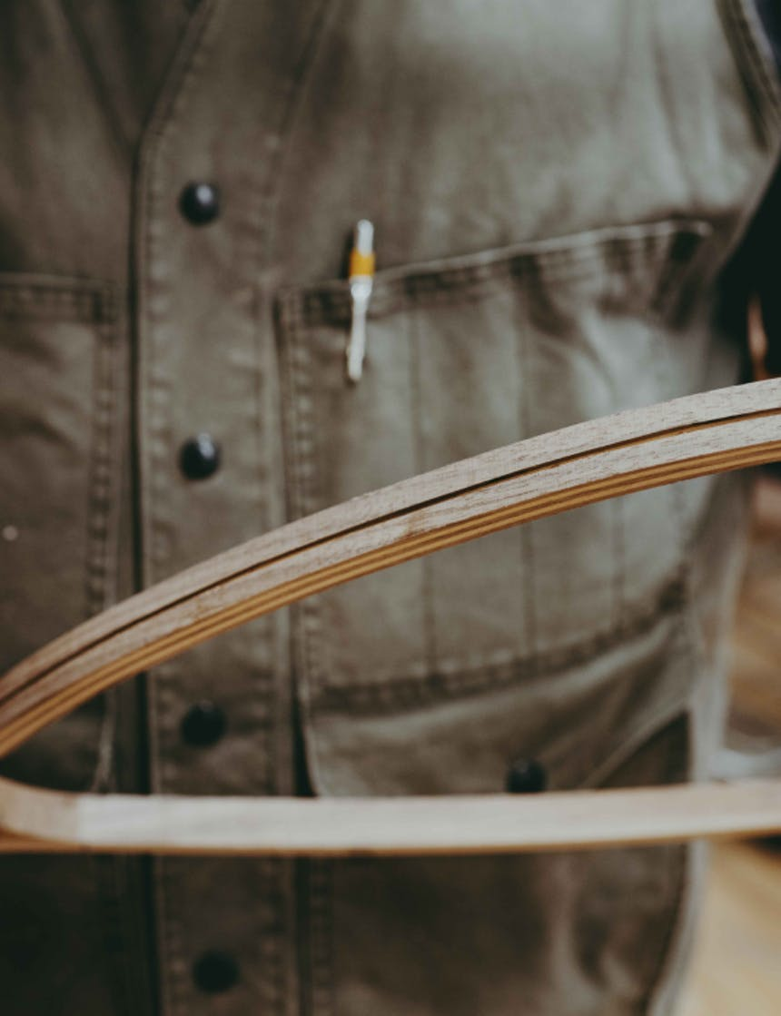 a close up of the woodworker wearing a green vest with the yellow mechanical pencil in his chest pocket while he holds the wooden net close to the camera