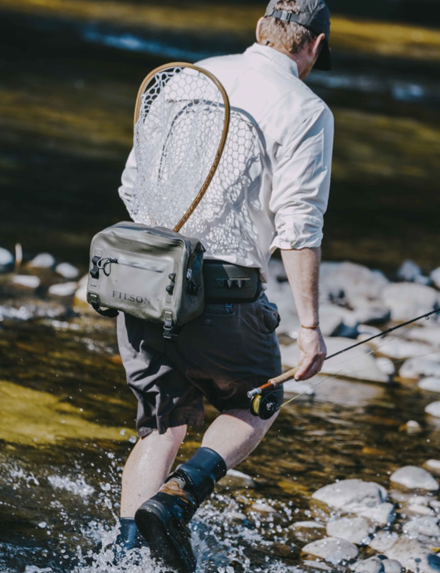 view from behind a white man wearing a white long sleeve button up with the sleeves rolled, dark grey shorts, a green dry waist pack with a wooden fishing net tucked in while he holds a fly fishing rod walking into a river